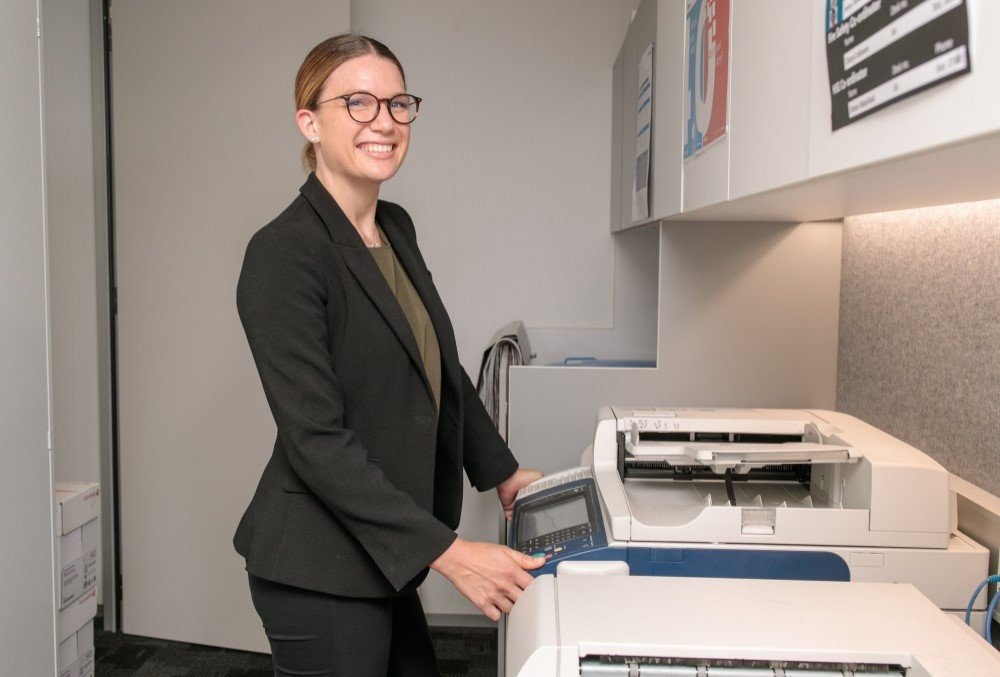 Worley Graduate - Young female professional using a photocopier.