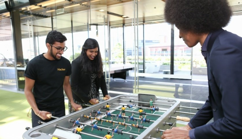 Commonwealth Bank graduates playing table soccer.