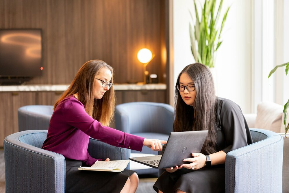 Two young professionals discussing something on a laptop