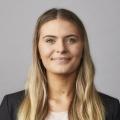 Coles Graduate - Young blonde female professional in black coat.