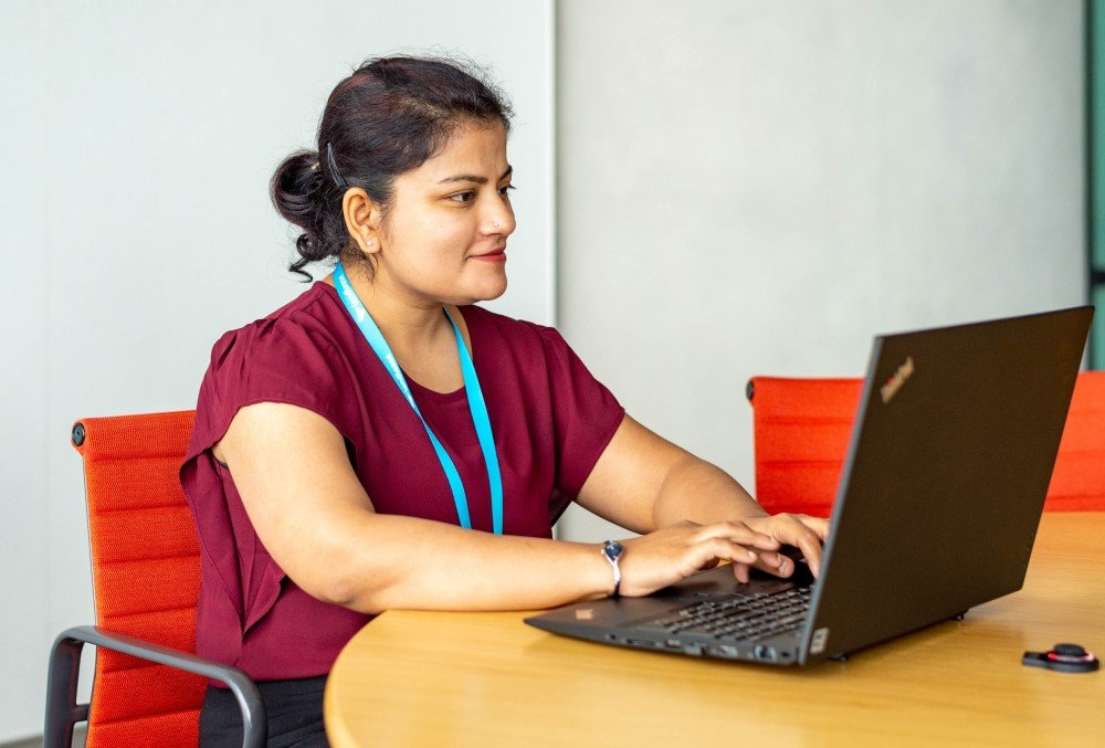 The Data School Graduate - Female professional working on her laptop.